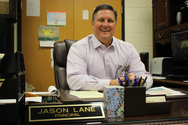 Greg Cantrell sitting at Principal Jason Lane's desk in Lane's office.