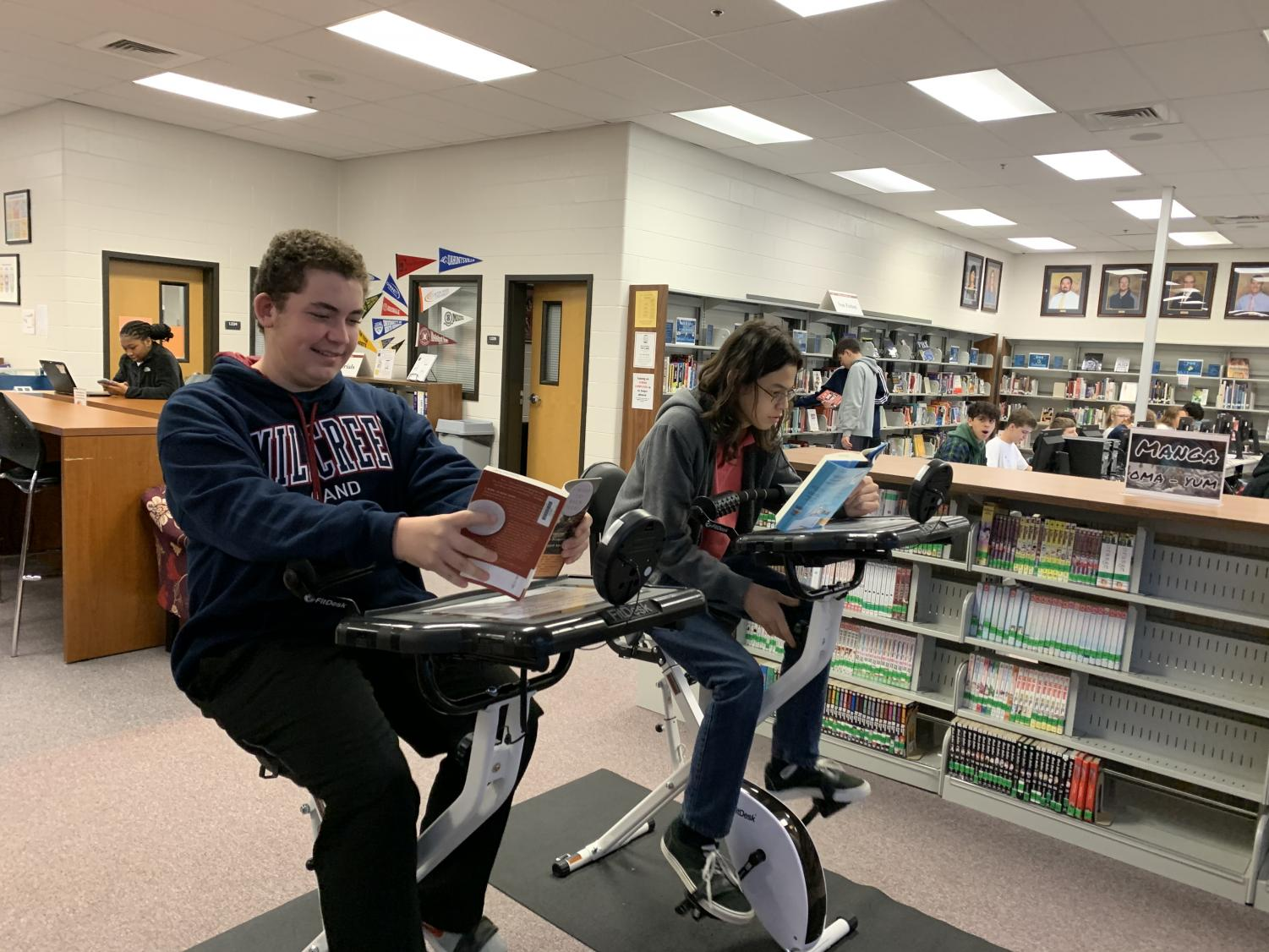 Students Cade Jones, 9, and Matthew Willis, 9, reading books while riding bikes in the media center