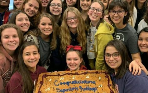 The Advanced Women's Chorus celebrating their superior ratings on their LGPE performances with a cookie cake