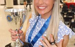 Kaylie at the Mill Creek Cheerleading Banquet posing with her State champion ring